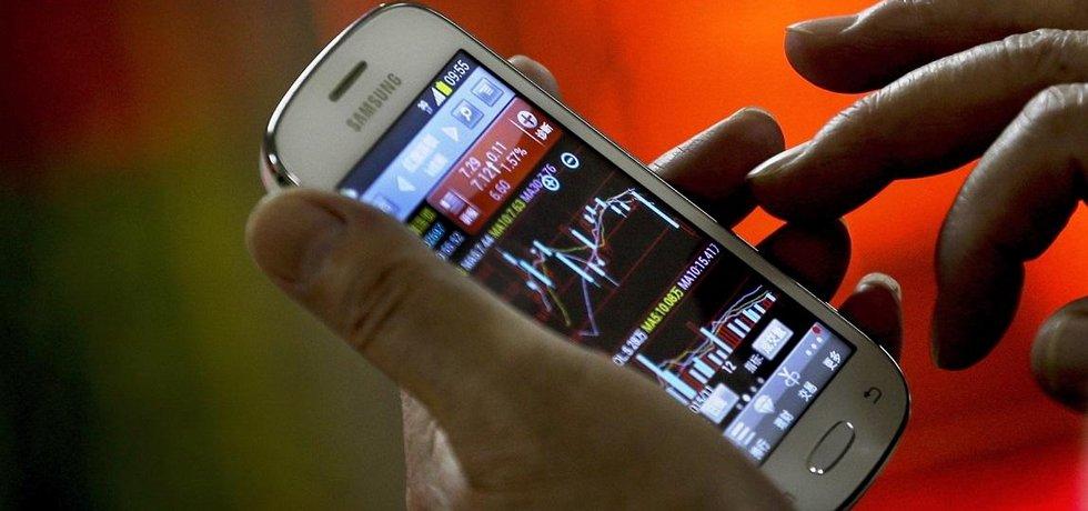 Investor sleduje akciové grafy