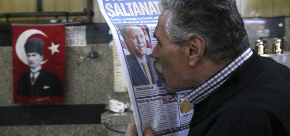 Příznivec tureckého prezident Recepa Tayyipa Erdogana libá jeho fotografii v novinách po drtivém volebním vítězství Erdoganovy strany