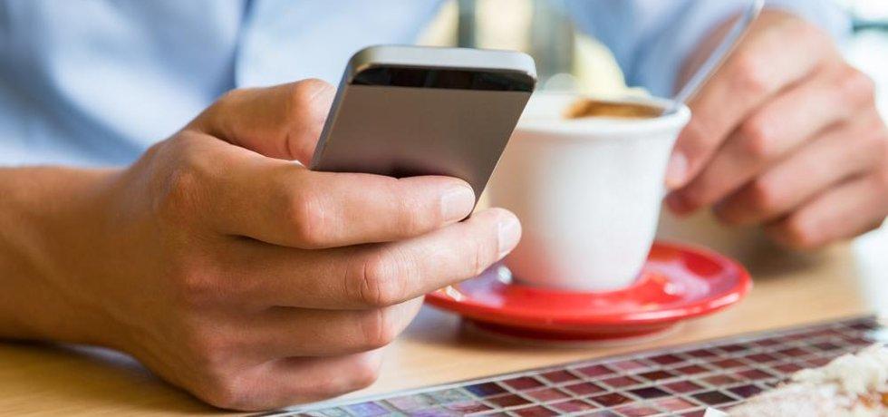 Ruka s mobilem u kafe