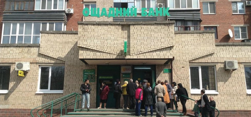 Lidé stojícíí ve frontě do pobočky ukrajinské banky Oschadbank.