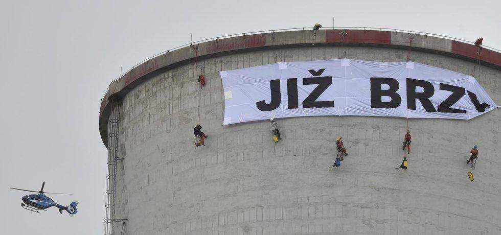 """Před polednem aktivisté na věži rozvinuli první část transparentu s nápisem """"Již brzy"""", druhou část prý vyvěsí v úterý."""