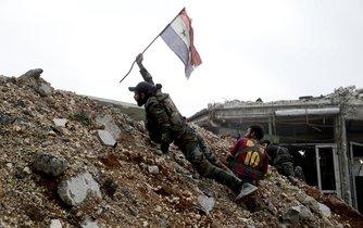 Syrský voják s vlajkou během bitvy s povstalci východně od Halabu.