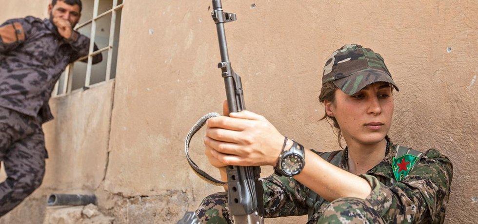 Chaos. Kurdská bojovnice Zelan Dirbeseyová patří k řadám syrských levicových jednotek YPJ. Na kurdských územích v Sýrii, kde jsme společně pracovaly na frontové linii, vládne dost nepřehledná situace. Oblast ovládá levicově orientovaná milice YPG, v podstatě odnož známější PKK (Kurdské strany pracujících), jež působí v Iráku. Portréty společného vůdce Abdulláha Očalana visí všude včetně rozbitých lamp veřejného osvětlení. Rudé hvězdy doplňují i podobizny mučedníků, kteří padli za svou ideologii. YPG ale spolupracuje také i s režimem Bašára Asada a bojuje proti další z kurdských stran PDK, podporované Masúdem Barzáním z Iráku. Na kurdské oblasti navíc útočí Islámský stát, operuje tam i šíitské hnutí Hizballáh podporované Íránem a svou roli hraje také Fronta an-Nusrá.