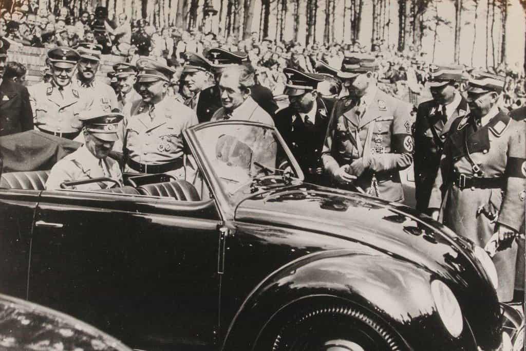 Vůdce je spokojen. Adolf Hitler si prohlíží první Volkswagen. Ferdinand Porsche stojí u předních dveří.
