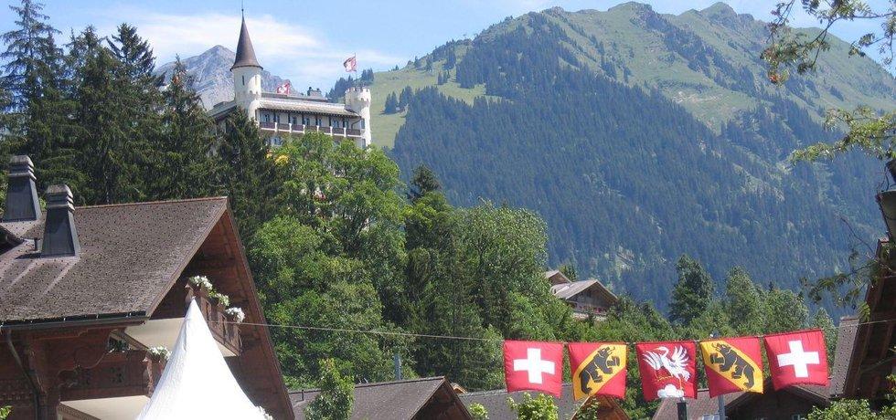 Gstaad (Švýcarsko). Věžovitá stavba za stromy je Gstaad Palace. Fotografie licencovaná pod CC BY 2.0