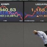 Obchodník na burze v Soulu se protahuje pod monitorem s aktuálním vývojem kurzů. Euro v Asii nadále ztrácelo a vůči dolaru se propadlo na novou nejnižší hodnotu za čtyři měsíce.