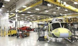 """Čekání na zákazníka. Zatímco stroj Bell 505 (v pozadí) už má finální nátěr, Bell 412 EPI zatím na nástřik čeká. Za slídami (vlevo) pak technici pod vodními tryskami otestují jeho """"nepromokavost""""."""