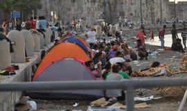 Za hradbami města Kos na stejnojmenném řeckém ostrově čekaly 15. srpna večer desítky uprchlíků zejména ze Sýrie na otevření trajektu, který se má stát jejich nouzovým střediskem.