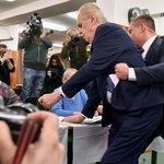 Ochranka zasahuje proti ženě, která se ve volební místnosti v pražských Lužinách vysvlékla a vrhla se směrem k prezidentovi Miloši Zemanovi (uprostřed), který přišel 12. ledna odevzdat hlas v prvním kole prezidentských voleb. Zeman z místnosti podporován ochránci odešel. Po několika minutách se prezident vrátil.