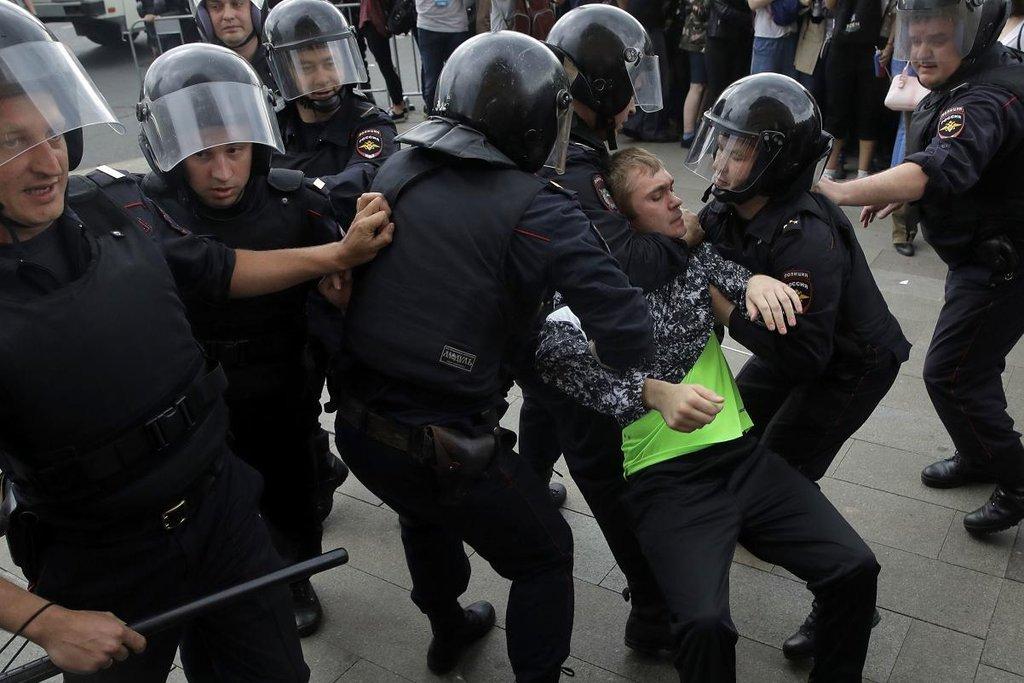 Ruští policisté odvádějí zadrženého demonstranta