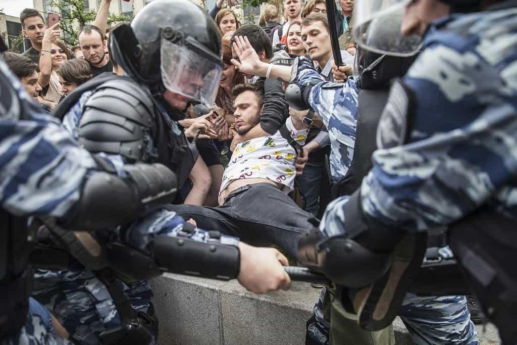 Policisté se snaží vytrhnout jednoho z davu protestantů na demonstraci v Moskvě