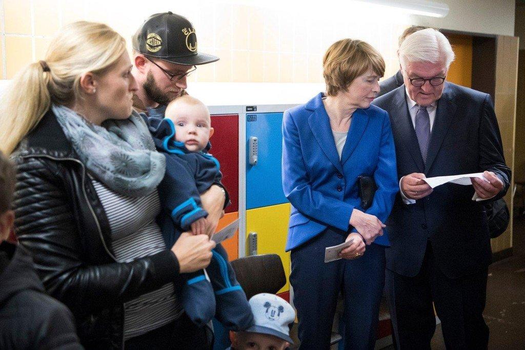 Německý prezident Frank-Walter Steinmeier čeká s manželku ve frontě ve volební místnosti v Berlíně, aby mohl hlasovat