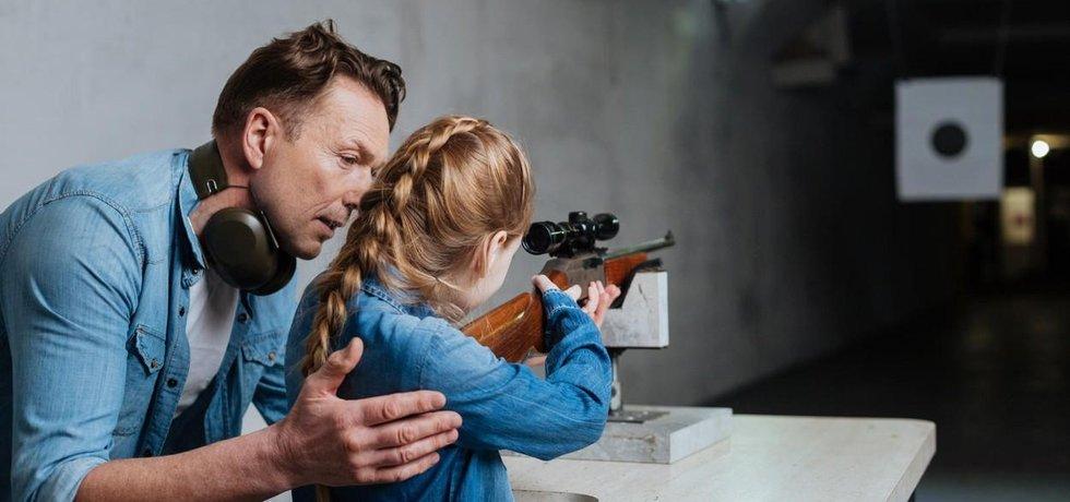 Starostlivý otec učí dceru střílet. V Americe běžný výjev