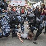 Tvrdý zásah. Dva policisté zajišťují jednoho z demonstrantů