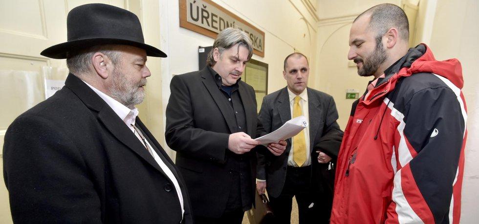 Advokát Jan Švarc, reportéři Pavel Kofroň a Miroslav Dobeš a tlumočník a překladatel Adam Homsi na chodbě soudu