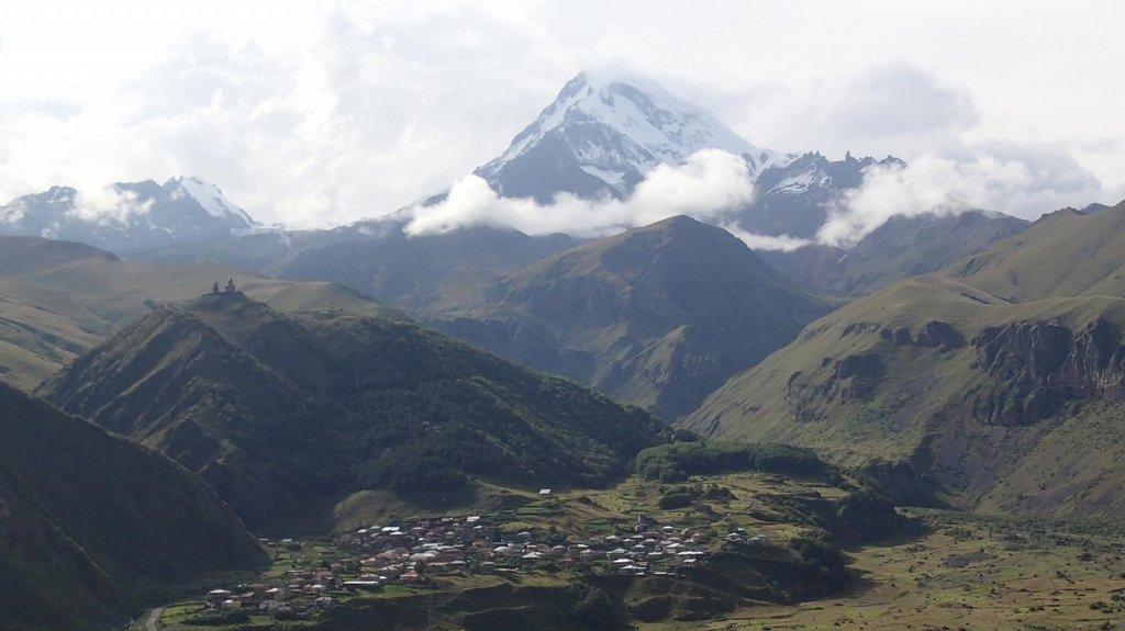 Horská vesnice Kazbegi, první zastávka v Gruzii po přejezdu ruské hranice. Nad vesnicí se tyči mohutný Kazbek (5033 m)