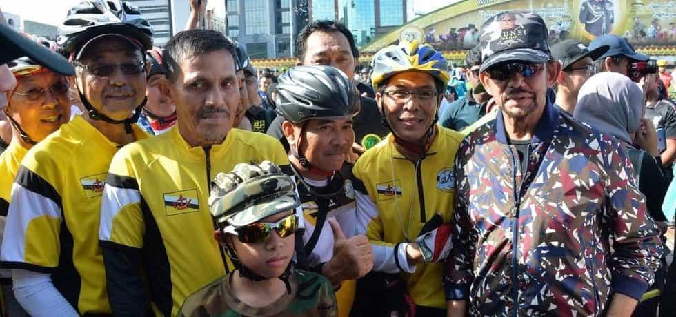 Sultán Hassanal Bolkiah (vpravo) pózuje s cyklisty v hlavním městě Bruneje Bandar Seri Begawan 3. září 2017.