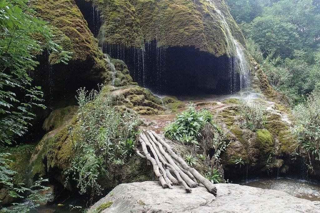 Stezka vede krásným údolím s vodopádem a jeskyní.