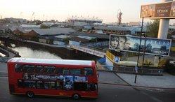 Olympijský atletický stadion a věž Orbit se vypínají nad moře střech východního Londýna, který byl dosud chudou čtvrtí dílen a skladišť.