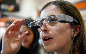 Návštěvnice si zkouší headset systému tzv. rozšířené reality (AR) na veletrhu v londýnském Excel Centre.
