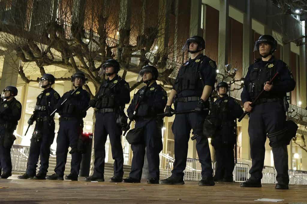 Budovu univerzity musela před rozlícenými demonstranty chránit policie.