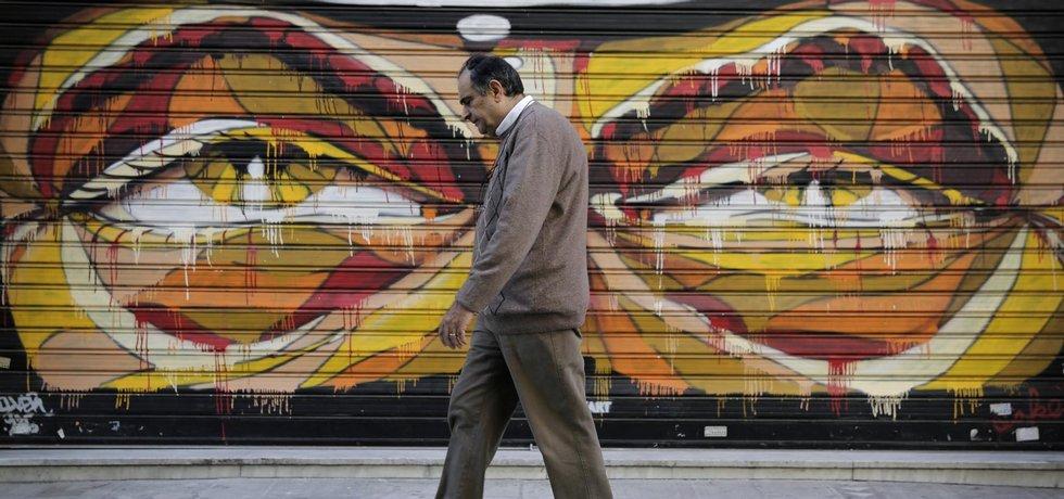 Muž prochází kolem grafitti v řecké metropoli Aténách