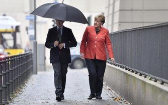 Německá kancléřka Angela Merkelová přichází se svým mužem k budově menzy, kde za velkého zájmu médií vhodila do urny hlasovací lístek