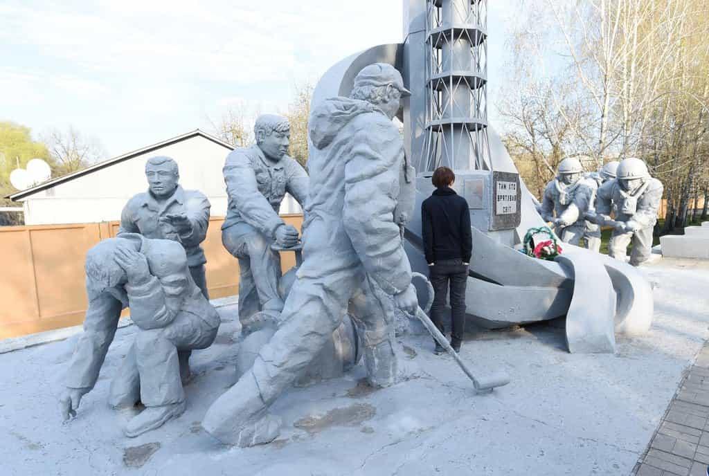 Památník záchranářům z Černobylu. Do místa po vybuchlém reaktoru se vydali v protichemických oblecích. Radiační v komunistické jaderné elektrárně nebyly