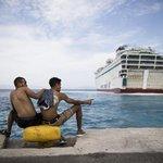 Migranti hledí na trajekt, který jim poskytne dočasné ubytování