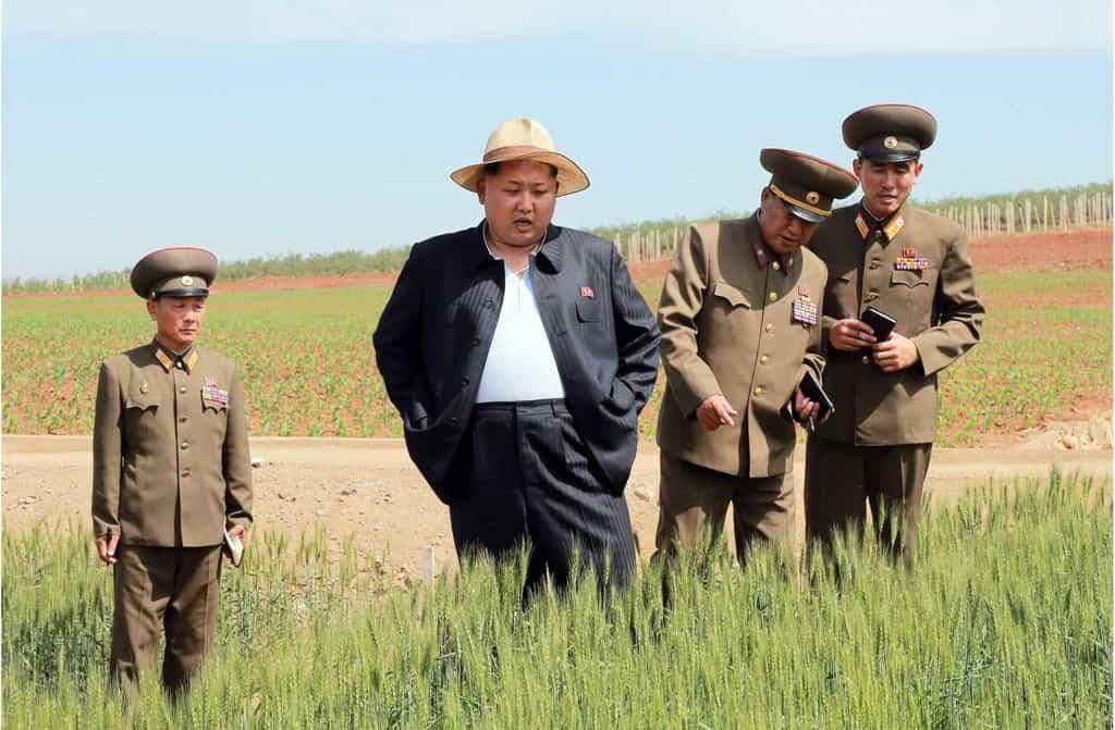 Kim ve společnosti armádních představitelů na inspekci farmy pro výzkum zemědělských semen.