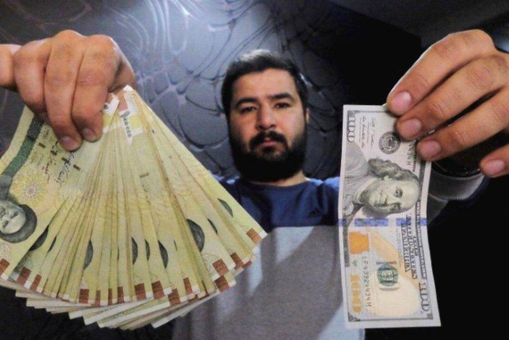 Je libo valuty? Íránský směnárník drží v pravé ruce svazek rijálů, v levé jeho protihodnotu v dolarech.