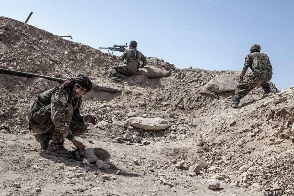 Malý opevněný post nad řekou Eufrat. V popředí jeden z vojáků SDF hladí štěně, zatímco jeho kolega pálí na pozice IS
