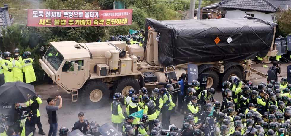 Americké armádní auto přiváží další ze součástí obranného protiraketového systému THAAD do jihokorejského Seongju. Jihokorejská policie drží stranou protestující pacifisty