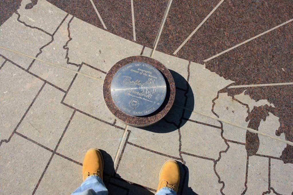 """Když se Havaj stala 50. americkým státem, byl určen nový střed země, a to v Belle Fourche v Jižní Dakotě. V roce 2008 tam město postavilo obrovský žulový kompas označený jako """"geografický střed národa"""". Ten se stal oblíbeným místem k návštěvě a pořizování fotografií. Problém je v tom, že skutečný střed USA (včetně Aljašky a Havaje) je asi o 32 kilometrů dál na sever na soukromém pozemku."""