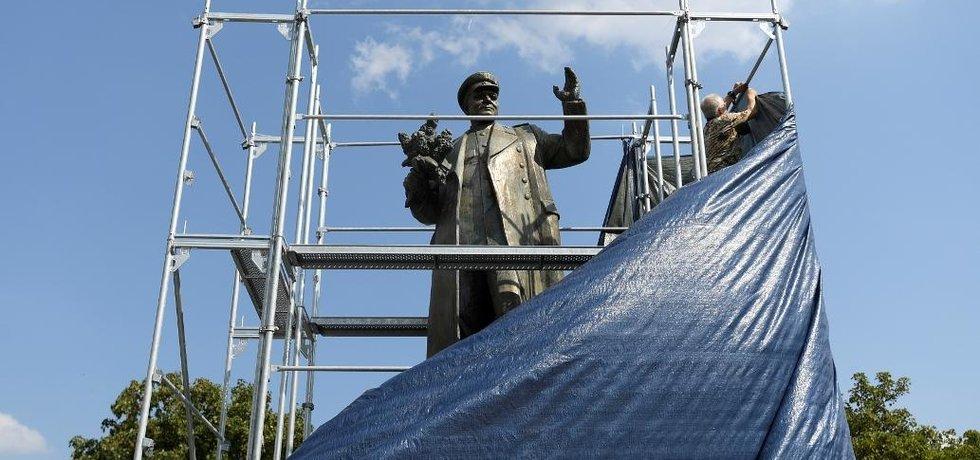 Neznámý muž odstraňuje plachtu z lešení kolem pomníku maršála Koněva.