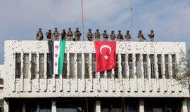 Turečtí vojáci a jejich syrští spojenci spouští vlajky obou zemí ve městě Ras al Ayn opuštěném kurdskými bojovníky.
