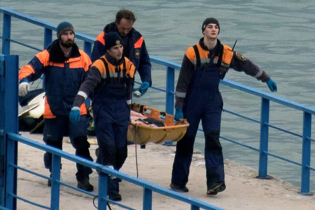 Záchranáři nesou tělo jedné z obětí pádu ruského letounu Tu-154