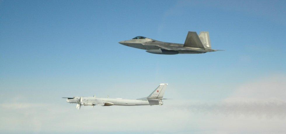 Ruský strategický bombardér Tu-95 Bear a americká neviditelná stíhačka F-22 Raptor