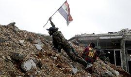 Syrský voják s vlajkou během bitvy s povstalci východně od Halabu
