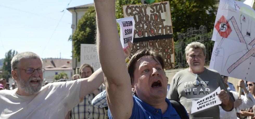 Odpůrci kancléřky Merkelové protestují proti její návštěvě Prahy nedaleko sídla Úřadu vlády ČR (Zdroj: ČTK)