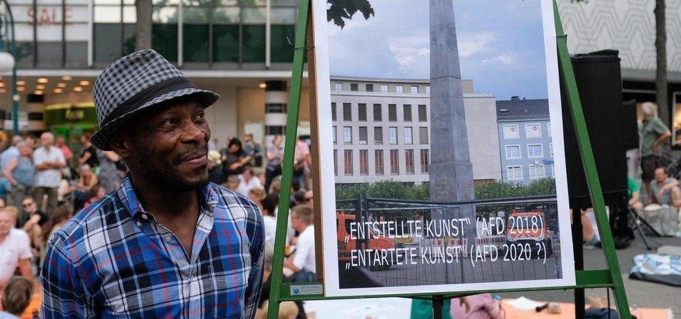 Umělec Olu Oguibe s fotkou pomníku.