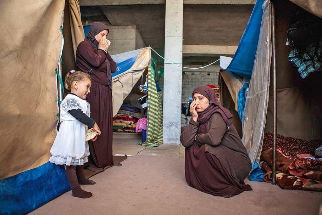"""Smutek. Třicetiletá Chalída utírá slzy: """"Než žít takhle, bylo by lepší, kdyby nás tehdy zabili."""" Spolu s dalšími čtyřmi jezídkami  přežívá v prvním patře nedostavěné budovy v iráckém Irbílu. Ženy uprchly ze Sindžáru, jejich manžele zabili stoupenci IS. V hrubých stavbách se tísní tisíce uprchlíků. Pomoc se k nim dostává obtížně, protože často nejsou registrovaní"""