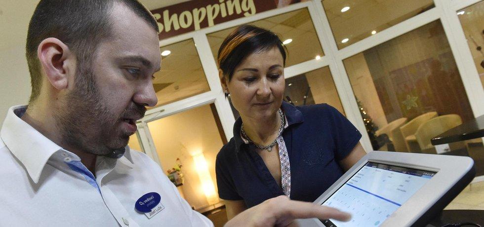 Jitka Kovarovičová z kavárny Cafe Shopping v Břeclavi začala od 1. prosince používat přístroj pro elektronickou evidenci tržeb (EET). Kvůli tomu také od dnešního dne zdražila sortiment. Na snímku vlevo je servisní technik O2 Josef Luža při nastavování přístroje.
