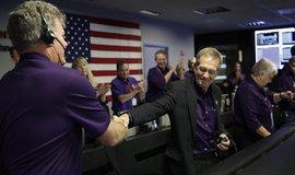 Projektový manažer Earl Maize (uprostřed) si třese rukou s Bileml Heventhalem v řídicím středisku NASA