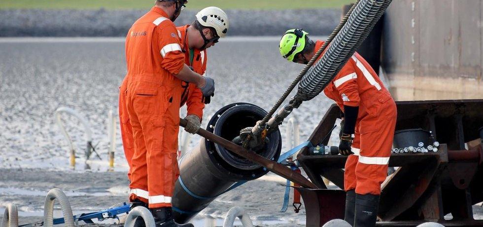 Konec 516 kilometrů dlouhého podmořského kabelu vytahuje loď na břeh v Büsumu na severu Německa