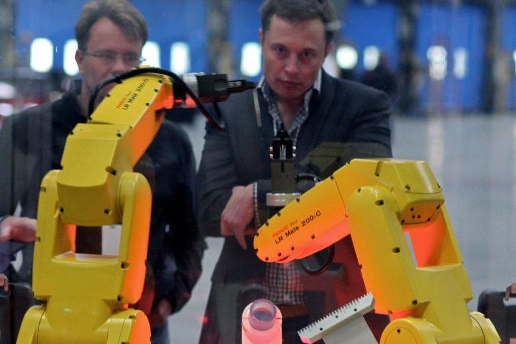 Elon Musk pozoruje roboty při demo ukázce kompletace vozů Tesla v roce 2010.